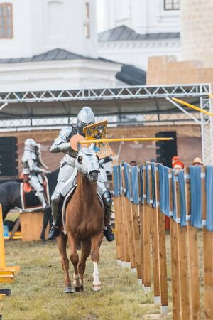 BULGAR, RUSSIA 11-08-2019: Knight Tournament at the medieval festival outdoors - a participant riding a horse in full armor and aiming in the opponent with a wooden spear
