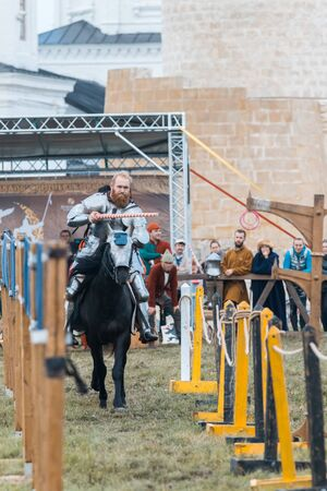 BULGAR, RUSSIA 11-08-2019: Knight riding a horse through the path and about to take the ring from the fence using a spear - medieval festival