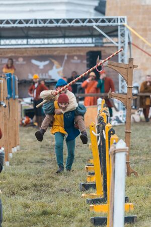 BULGAR, RUSSIA 11-08-2019: Two buffoons having fun on the battlefield on medieval festival - holding a wooden spear