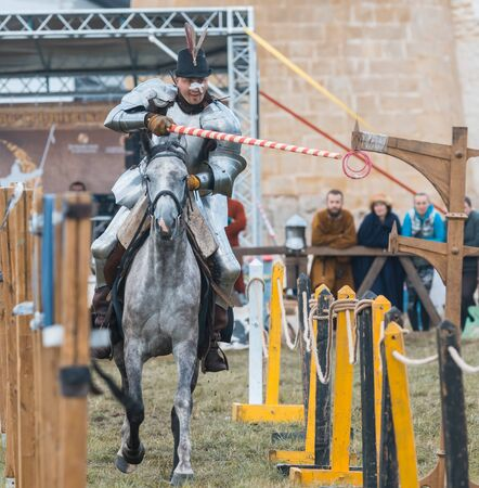 BULGAR, RUSSIA 11-08-2019: Knight riding through the path and takes the ring from the fence with a spear - medieval festival