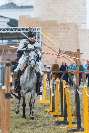BULGAR, RUSSIA 11-08-2019: Knight riding through the path and takes the ring from the fence with a spear