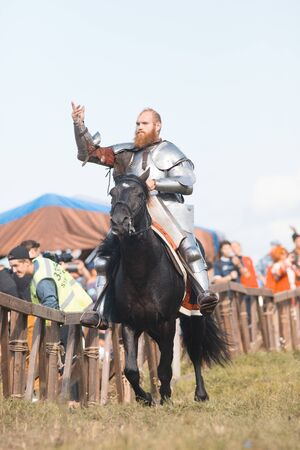 BULGAR, RUSSIA 11-08-2019: Knight riding a horse near the fence and communicates with the audience