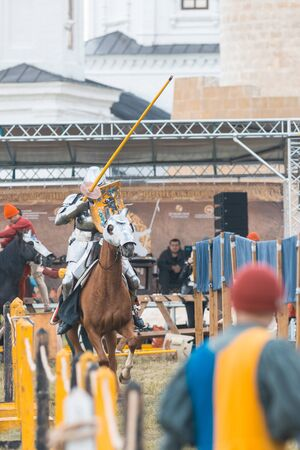 BULGAR, RUSSIA 11-08-2019: Knight Tournament at the medieval festival - man riding a horse in full armor and aiming in the opponent with a wooden spear 新聞圖片
