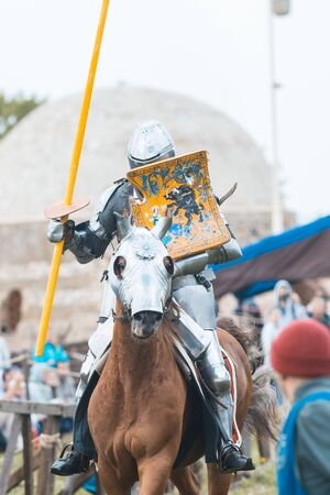 BULGAR, RUSSIA 11-08-2019: Knight Tournament at the medieval festival - man riding a horse in full armor and holding a spear 新聞圖片