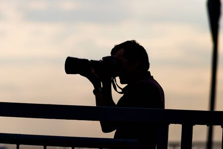 Photographer silhouette on a background of early sunset