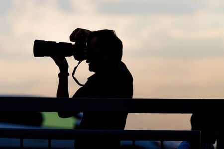 Photographer silhouette with his camera on a background of early sunset 스톡 콘텐츠 - 129774426
