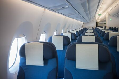 An economy class clean cabin of the airplane - empty blue chairs - opened portholes Фото со стока