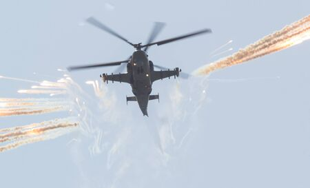 A military combat helicopter spreads a smoke screen using smoke bombs. Mid shot