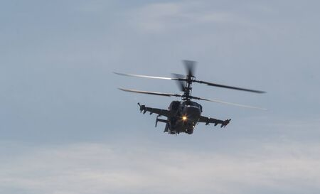A military combat helicopter with two pair of blades flying in the sky with lights on