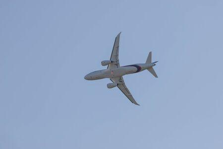 Big passenger white plane flying in the blue sky - bottom view
