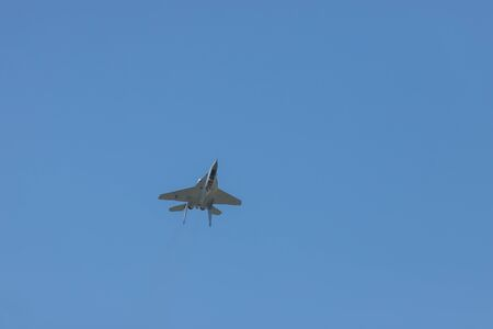 A military fighter jet flying in the sky upside down