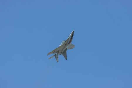 A gray military fighter jet flying in the sky upside down