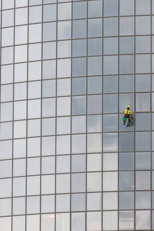 A man worker in worksuit cleaning the exterior windows of a skyscraper - industrial alpinism - hanging on ropes