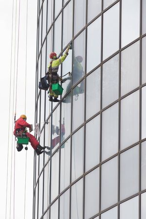 Two men workers hanging on ropes by the exterior windows of a skyscraper and cleansing them - industrial alpinism