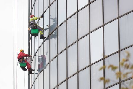 Two men workers in red and yellow suits hanging on ropes by the exterior windows of a skyscraper and cleansing them - industrial alpinism - overcast weather