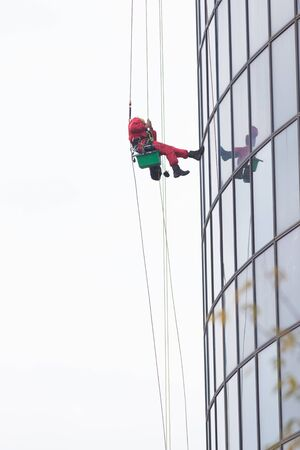 A man worker in red worksuit cleaning the exterior windows of a skyscraper - industrial alpinism at overcast weather - hanging on ropes