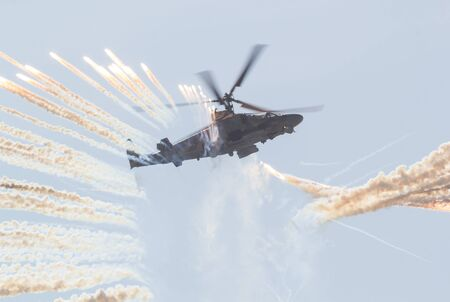 29 AUGUST 2019 MOSCOW, RUSSIA: A military combat helicopter spreads a smoke screen using smoke bombs
