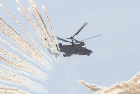 29 AUGUST 2019 MOSCOW, RUSSIA: A military combat helicopter with two pair of blades spreads a smoke screen using smoke bombs 에디토리얼