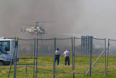 29 AUGUST 2019 MOSCOW, RUSSIA: A big fire helicopter spreads a water stream on the smoky ground - police men watching it