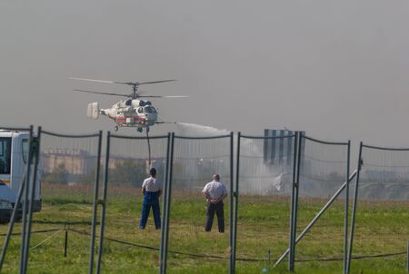 29 AUGUST 2019 MOSCOW, RUSSIA: A big fire helicopter spreads a water on the smoky ground - police men watching it