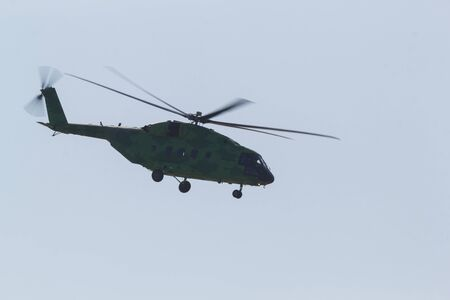 30 AUGUST 2019 MOSCOW, RUSSIA: A green military coloring helicopter flying in the sky - side view