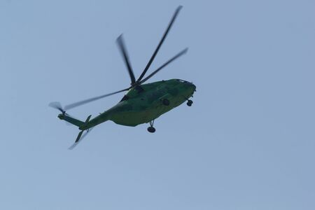 30 AUGUST 2019 MOSCOW, RUSSIA: A green military coloring helicopter flying in the sky - side behind view