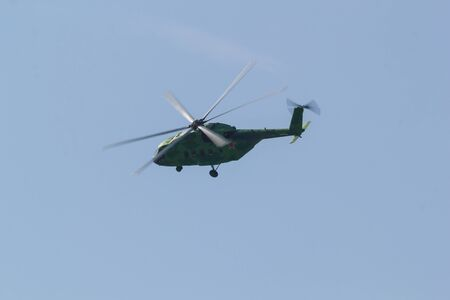 30 AUGUST 2019 MOSCOW, RUSSIA: A green military coloring helicopter with red star on the corpus flying in the sky - side view