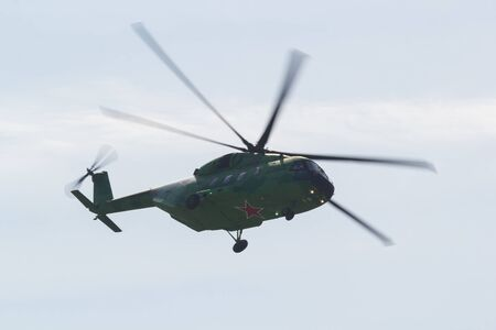 30 AUGUST 2019 MOSCOW, RUSSIA: A green military coloring helicopter with red star on the corpus at the bottom flying in the sky