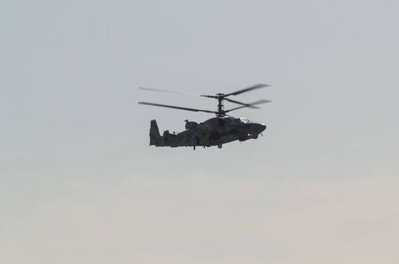 29 AUGUST 2019 MOSCOW, RUSSIA: A military dark helicopter with two pair of blades flying in the sky 에디토리얼