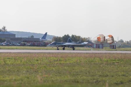 29 AUGUST 2019 MOSCOW, RUSSIA: Reactive fighter jet landing on the runway and slows down using parachutes