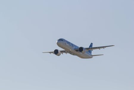 30 AUGUST 2019 MOSCOW, RUSSIA: Big passenger aircraft flying in the clear blue sky - front side view - AIRBUS MC-21 300