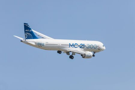30 AUGUST 2019 MOSCOW, RUSSIA: Big passenger aircraft flying in the clear blue sky - side view of the corpus - AIRBUS MC-21 300 에디토리얼