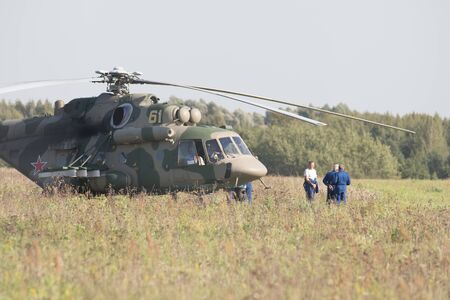 29 AUGUST 2019 MOSCOW, RUSSIA: A military green helicopter standing on the field - three working men standing by it