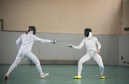 Two young women fencers having a training at the gym Standard-Bild