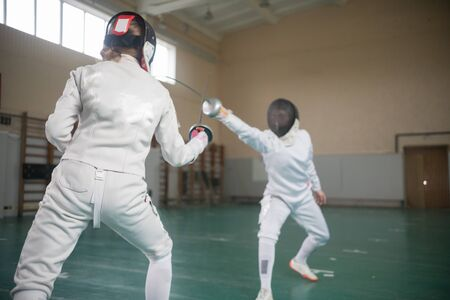 Two young women fencers having a training in full protection Standard-Bild