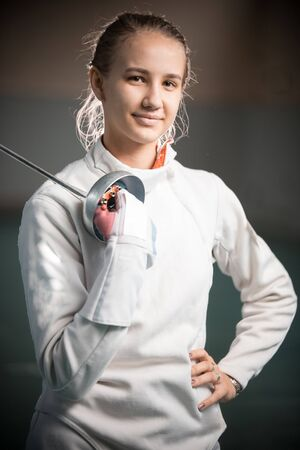 A portrait of a young woman fencer with a sword