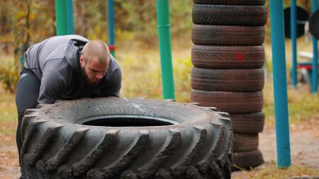 Tough tattooed man bodybuilder in gloves pushes over the truck tire on the ground - training in the autumn forest Stock fotó