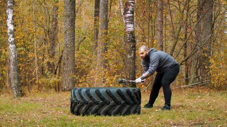 A tough man bodybuilder hitting the truck tire with a metal hammer - autumn forest