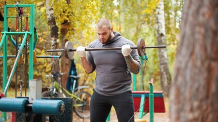 A man bodybuilder pumping his hands with the self-made dumbbells - training on the outdoors sports ground