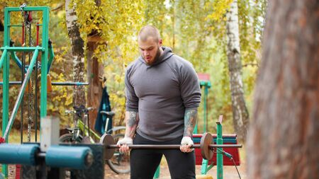 A man bodybuilder pulls up the self-made dumbbells - training on the outdoors sports ground