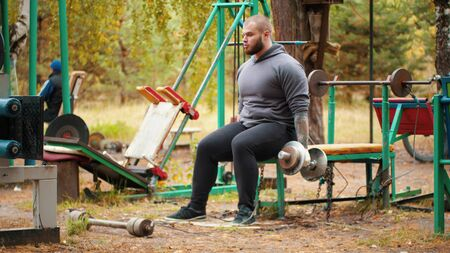 A man bodybuilder pulling the dumbbells in both hands - the dumbbells chained to the bench Stock fotó