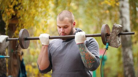 A man bodybuilder training on the outdoors sports ground - pulls the bar connected to the weights - autumn forest
