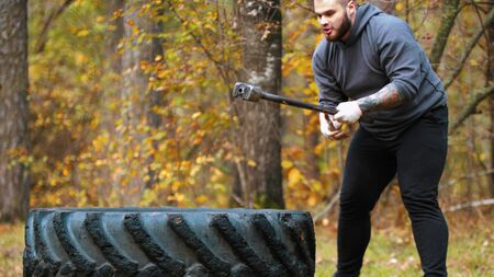 A big man bodybuilder hitting the truck tire with a metal hammer - autumn forest
