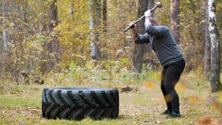 A man bodybuilder hitting the truck tire with a metal hammer - autumn forest