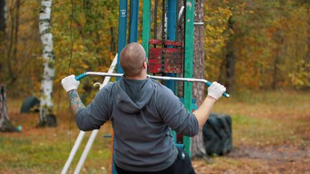 A man bodybuilder training on the outdoors sports ground - autumn forest
