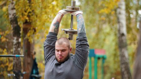 A man bodybuilder pumping his hands with the dumbbell behind his back - training on the outdoors sports ground