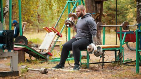 A man bodybuilder pulling the dumbbells in both hands in the forest