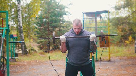 Ein Mannbodybuildertraining auf dem Sportplatz im Freien - Herbstwald.