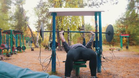 A man bodybuilder training on the outdoors kids sports ground - pulls up the dumbbells Stock fotó