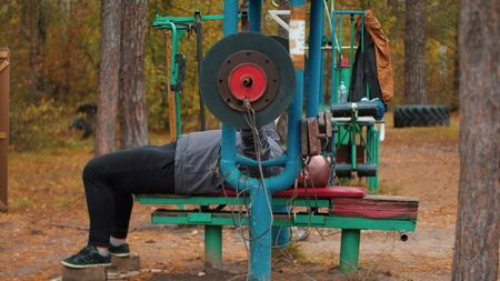 A man bodybuilder pulls up a huge dumbbell - training on the outdoors kids sports ground